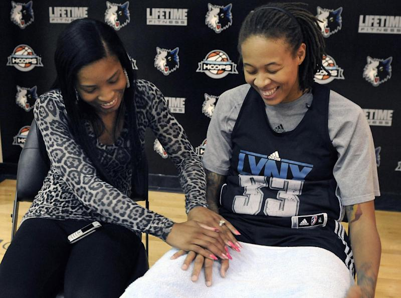 In this photo made Friday, Oct. 12, 2012, Minnesota Lynx WNBA basketball star and Olympic gold medalist Seimone Augustus, right, looks at the engagement right she gave LaTaya Varner, left, during an interview with The Associated Press in Minneapolis. With a wedding scheduled for May and a crucial vote in November that threatens to ban gay marriage in Minnesota, the intensely private Augustus is speaking out. (AP Photo/Jim Mone)