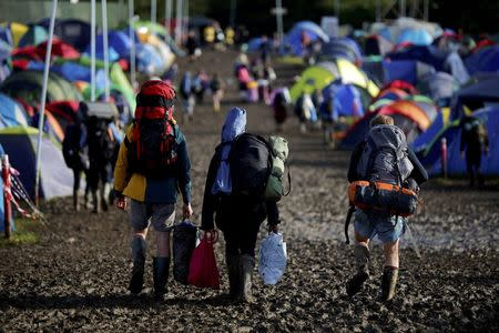 Revellers carry their belongings as they leave Worthy Farm in Somerset after the Glastonbury Festival