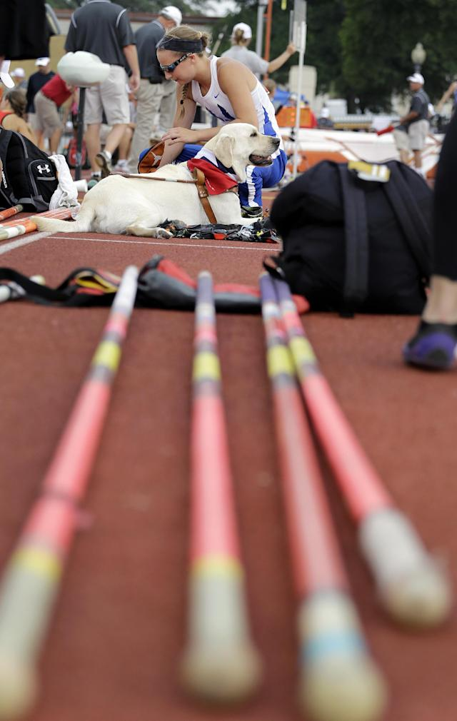 Emory Rains High School's Charlotte Brown with her guide dog, Darth Vader, as she competes in the Girls 3A pole vault in the UIL State Track & Field meet, Friday, May 9, 2014, in Austin, Texas. Brown, a pole vaulter who happens to be legally blind, starts on the clap from her coach and counts her steps on her approach. (AP Photo/Eric Gay)