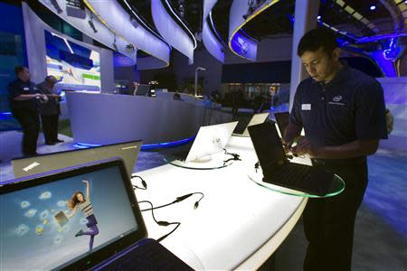 Raman Chari prepares a display of convertible Ultrabooks at the Intel booth prior to the opening of the Consumer Electronics Show (CES) in Las Vegas in this January 8, 2013 file photo. REUTERS/Steve Marcus/Files