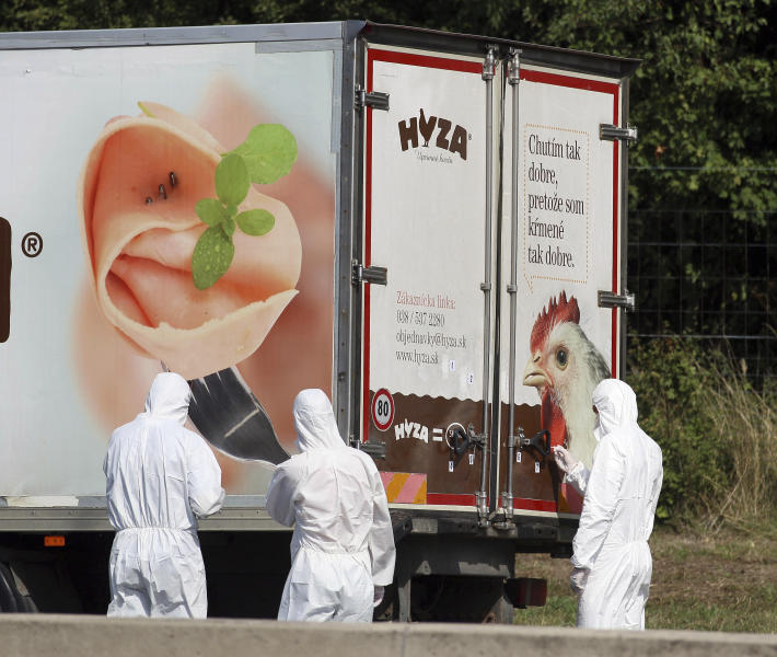 FILE - In this Thursday, Aug. 27, 2015 file photo, investigators stand near an abandoned truck on the shoulder of Highway A4 near Parndorf, Austria, south of Vienna. A Hungarian court has extended the prison sentences of four human traffickers convicted last year for their roles in a 2015 in which 71 migrants suffocated to death in the back of a refrigerated truck found on a highway in Austria. (AP Photo/Ronald Zak, file)
