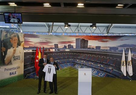 Gareth Bale (L) of Wales hold his new Real Madrid soccer club jersey accompanied by president Florentino Perez at the Santiago Bernabeu stadium in Madrid, September 2, 2013. REUTERS/Sergio Perez