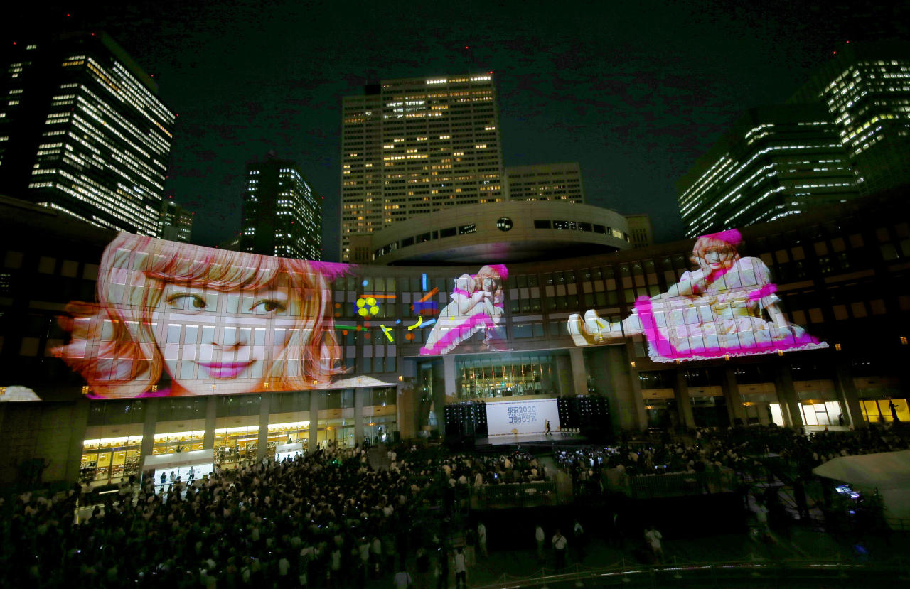 Images of Japanese fashion model and singer Kyary Pamyu Pamyu are projected on the Tokyo Metropolitan Government building during the Tokyo 2020 flag tour festival for the 2020 Games in Tokyo, Monday, July 24, 2017. Japan began its three-year countdown to the Olympics on Monday with concerts, races and other events meant to drum up public enthusiasm for the games. The 2020 Games will be Japan's first summer Olympics since the 1964 edition in Tokyo. (AP Photo/Shizuo Kambayashi)