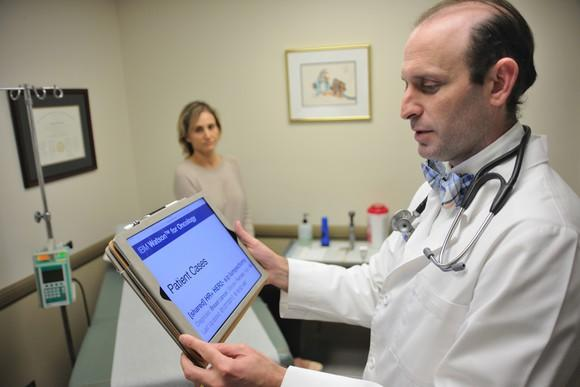 A doctor using a tablet computer, with a patient in the background