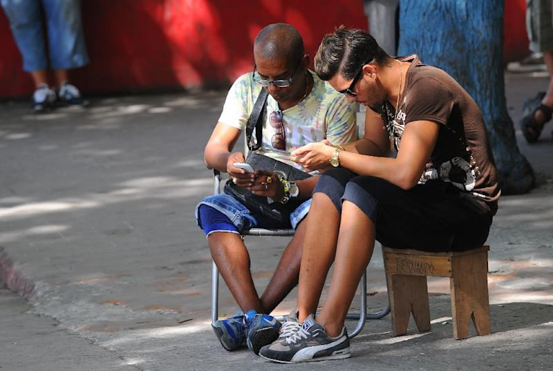 Cubans use their mobile devices to connect to the Internet via wifi in a street in Havana, on July 2, 2015 (AFP Photo/Yamil Lage)
