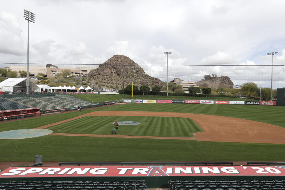 A grounds crew member applies fertilizer to the field as players report for spring training baseball, Tuesday, Feb. 11, 2020, in Tempe, Ariz. Los Angeles Angels pitchers and catchers start practice on Wednesday. (AP Photo/Darron Cummings)