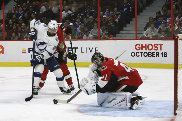 Ottawa Senators goaltender Craig Anderson (41) scoops the puck up in front of Tampa Bay Lightning right wing Nikita Kucherov (86) as Senators defenceman Nikita Zaitsev (22) defends during first period of NHL hockey action in Ottawa, Saturday, Oct. 12, 2019. (Fred Chartrand/The Canadian Press via AP)