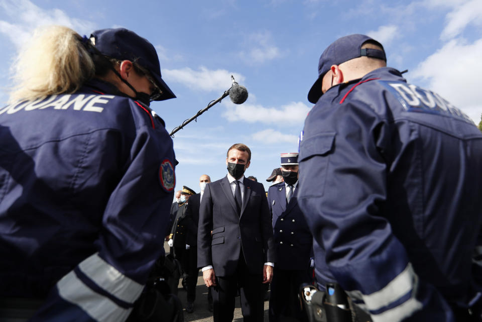 French President Emmanuel Macron speaks with French police officers during a visit on the strengthening border controls at the crossing between Spain and France, at Le Perthus, France, Thursday, Nov. 5, 2020. (Guillaume Horcajuelo, Pool via AP)