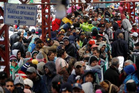 Venezuelan migrants stand in line to register their exit from Colombia before entering into Ecuador, at the Rumichaca International Bridge