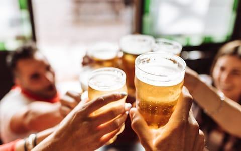 Group of friends toasting the beer in a pub