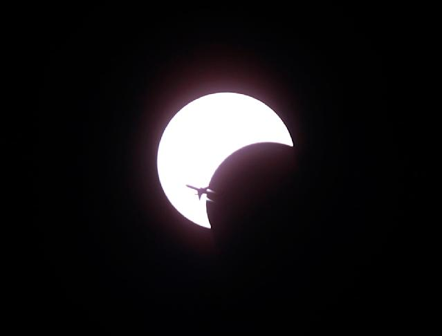 An aircraft flies past a solar eclipse in Bangkok January 15, 2010. The annular eclipse of the sun, which will last for over 11 minutes during its maximum duration, will be visible from a 300-km wide track that passes half of the earth, according to NASA. REUTERS/Chaiwat Subprasom (THAILAND - Tags: SOCIETY ENVIRONMENT SCI TECH TRANSPORT IMAGES OF THE DAY)