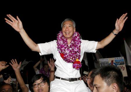FILE PHOTO  Singapore's Prime Minister and Secretary-General of the People's Action Party Lee Hsien Loong (C) celebrates with supporters after the general election results at a stadium in Singapore September 12, 2015.  REUTERS/Edgar Su/File Photo