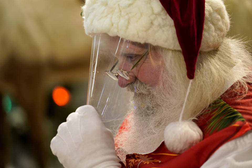 Santa Claus adjusts his protective face shield between visits from children and their families at Bass Pro Shops, in Miami on Nov. 20, 2020. In this socially distant holiday season, Santa Claus is still coming to towns (and shopping malls) across America but with a few 2020 rules in effect. (AP Photo/Lynne Sladky)