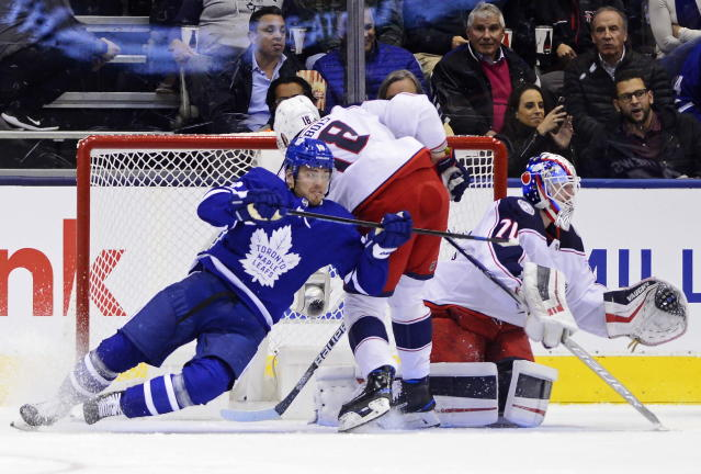 Toronto Maple Leafs left wing Andreas Johnsson (18) and Columbus Blue Jackets left wing Pierre-Luc Dubois (18) battle next to Blue Jackets goaltender Joonas Korpisalo (70) during first-period NHL hockey game action in Toronto, Monday, Oct. 21, 2019. (Frank Gunn/The Canadian Press via AP)
