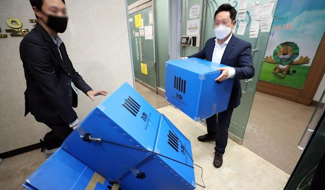 State prosecutors take away boxes containing possible evidence after conducting a search and seizure at Shincheonji's main office. Photo: EPA