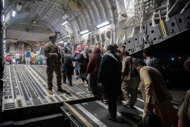 Afghans board a U.S. Air Force transport plane during an evacuation at Hamid Karzai International Airport in Kabul on Sunday. Officials told media Monday that Canada's special forces are currently working inside and outside the confines of the airport to ensure Canadians and eligible Afghans can get onto planes destined for Canada.  (U.S. Air Force/REUTERS - image credit)