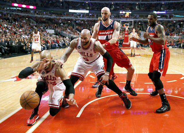 Chicago Bulls forward Taj Gibson (22) keeps the ball from going out of bounds as Carlos Boozer (5), Washington Wizards center Marcin Gortat (4) and Trevor Booker (35) stand near during the first half of Game 5 in an opening-round NBA basketball playoff series Tuesday, April 29, 2014, in Chicago. (AP Photo/Charles Rex Arbogast)