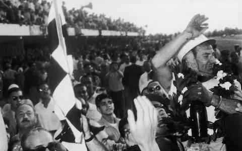 Stirling Moss celebrates victory in the 1958 Argentine Grand Prix - Credit: Hulton Archive