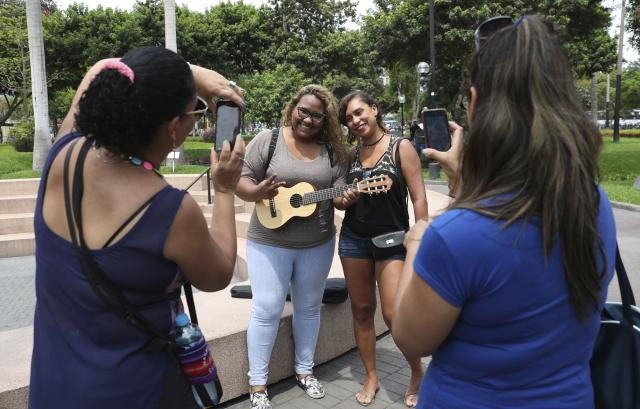 In this Dec. 28, 2018 photo, fans of Venezuelan singer Reymar Perdomo pose for photos with her after they noticed her doing a press interview at a park in the Miraflores area of Lima, Peru. Perdomo's life took a turn when she wrote a heartfelt reggae song about leaving her homeland that went viral on the internet and has brought tears to hundreds in the Venezuelan diaspora that has spread around the globe. (AP Photo/Martin Mejia)