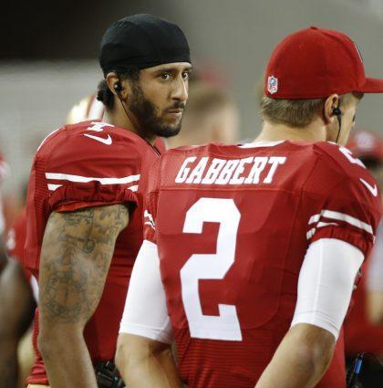 Colin Kaepernick, left, explains why he's refusing to stand during the national anthem (AP).