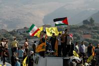 Hezbollah supporters lift its flags alongside those of Iran and Palestine, during an anti-Israel protest