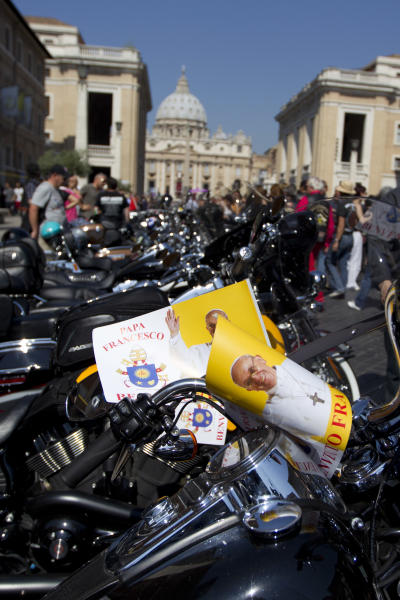 Harley Davidson motorcycles riders park their motorcycles in Via della Conciliazione leading to the Vatican, seen at top, as they wait for Pope Francis to drive by to bless them ahead of mass in St. Peter's Square, at the Vatican, Sunday, June 16, 2013. The riders are gathered in Rome for a four-day event to celebrate the motorcycle company's 110th anniversary. (AP Photo/Andrew Medichini)