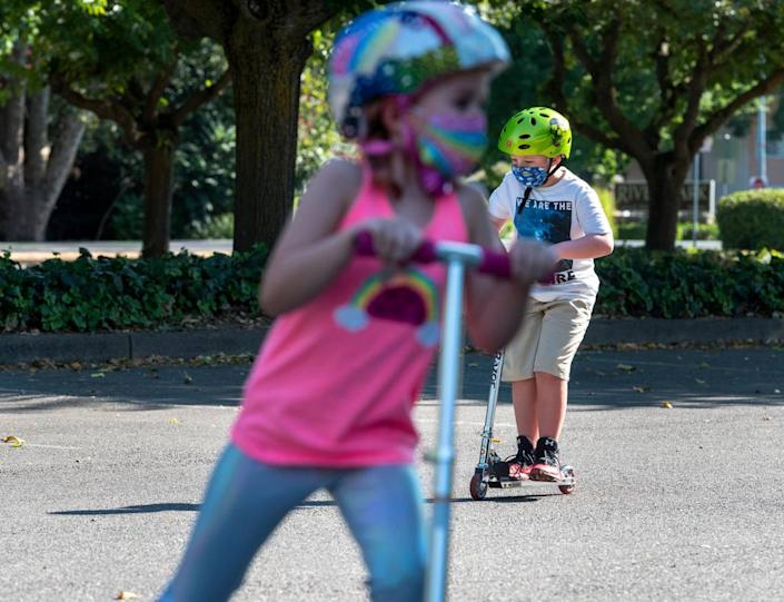 Violette Gottis, left, 7, and, Mason, 9, ride scooters in the Scottish Rite Masonic Center parking lot in East Sacramento on Thursday, July 23, 2020. Mason has chronic health conditions, including Type 1 diabetes and severe asthma, which elevate his risk from COVID-19. His mother plans to keep him out of school until there is a vaccine or more effective treatment.