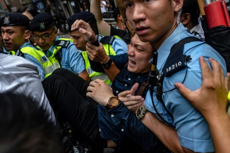 Pro-independence activist Wayne Chan is removed by police from outside the Foreign Correspondents' Club as people protest ahead of the speech by pro-independence activist Andy Chan in August