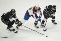 Los Angeles Kings center Trevor Moore (12) and center Blake Lizotte (46) defend against Colorado Avalanche center Nathan MacKinnon (29) during the second period of an NHL hockey game Thursday, Jan. 21, 2021, in Los Angeles. (AP Photo/Ashley Landis)