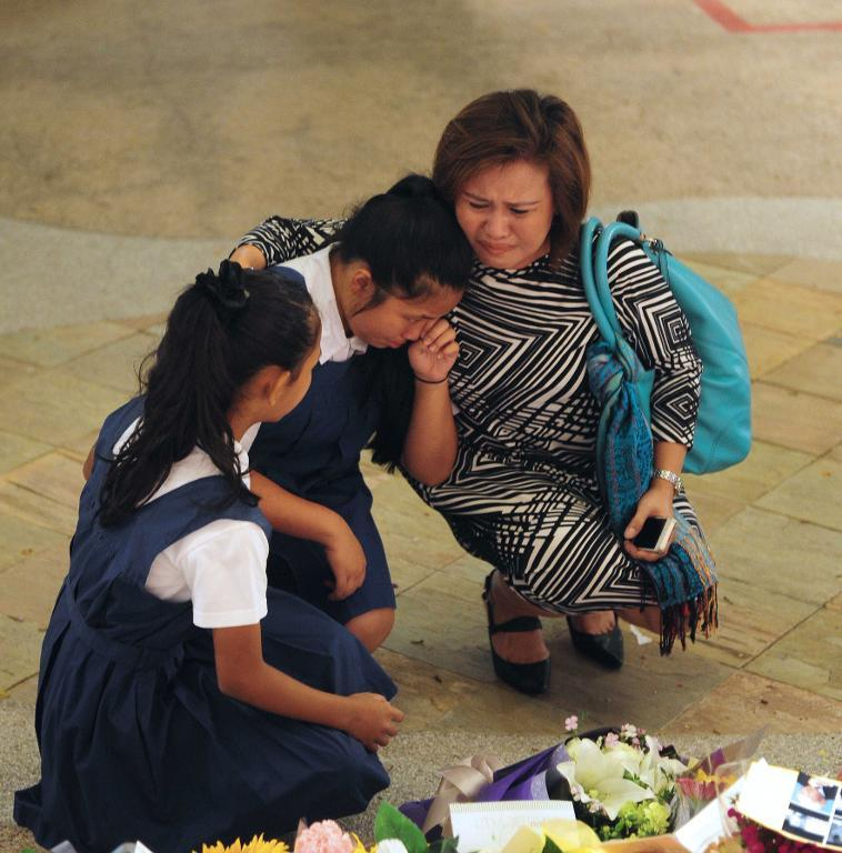 A family mourns outside the Singapore General Hospital, in honour of former prime minister Lee Kwan Yew, on March 23, 2015
