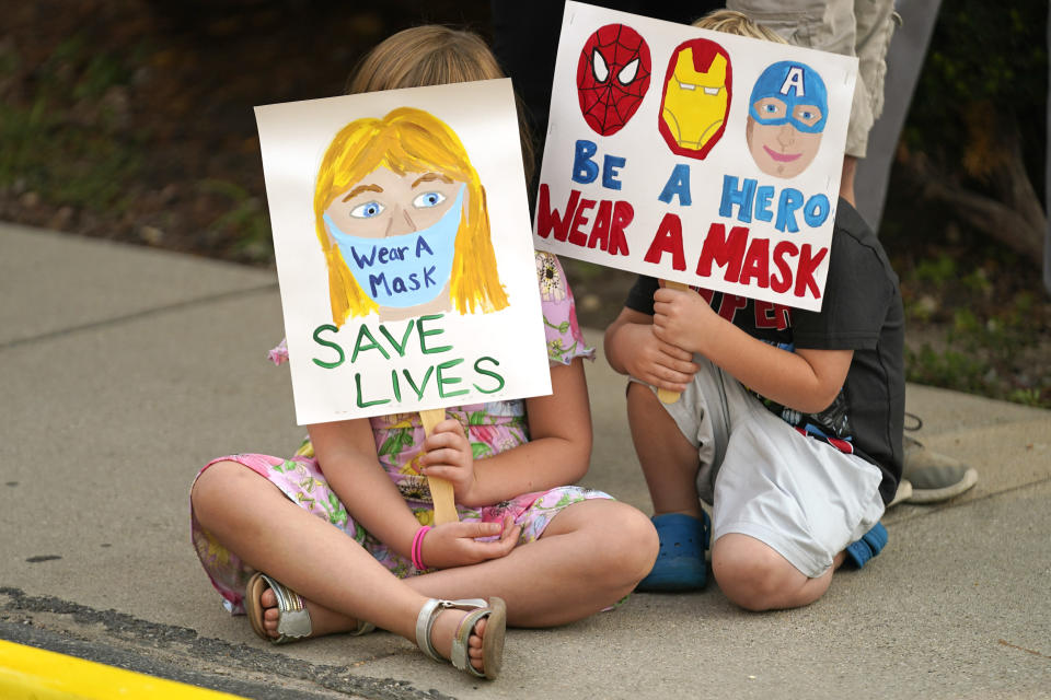 FILE - In this Aug. 6, 2021, file photo, Lucie Phillips, 6, and her brother David Phillips, 3, join parents and students during a rally at Utah State School Board Office calling for mask mandate in Salt Lake City. The mayor of Salt Lake City announced Friday, Aug. 20, 2021, that she had issued a mask order in the city's K-12 schools as the highly contagious delta variant of the coronavirus spreads. Mayor Erin Mendenhall said she used her emergency powers to issue the order and that she plans to work with health officials to determine when it can be lifted. (AP Photo/Rick Bowmer, File)