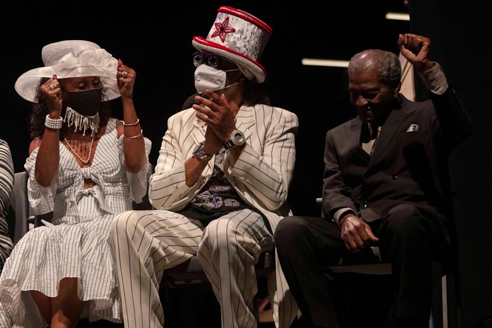 Otis Williams, part of the inaugural class of the Cincinnati Black Music Walk of Fame, raises his fist during the induction ceremony while sitting next to fellow inductee and funk artist Bootsy Collins on Saturday night in Cincinnati.