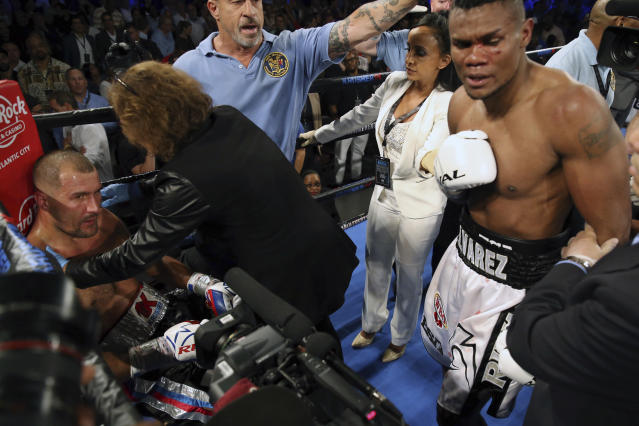 Eleider Alvarez, right, of Colombia, stands nearby as medical personnel tend to Sergey Kovalev, of Russia, after Alvarez knocked him out during the seventh round of their boxing bout at 175 pounds, Saturday, Aug. 4, 2018, in Atlantic City, N.J. (AP Photo/Mel Evans)