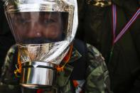 An anti-government protester wears a homemade tear gas mask during a rally near the Government House in Bangkok February 18, 2014. A Thai police officer was killed and dozens of police and anti-government protesters were wounded in gun battles and clashes in Bangkok on Tuesday, officials and witnesses said. REUTERS/Athit Perawongmetha (THAILAND - Tags: POLITICS CIVIL UNREST)