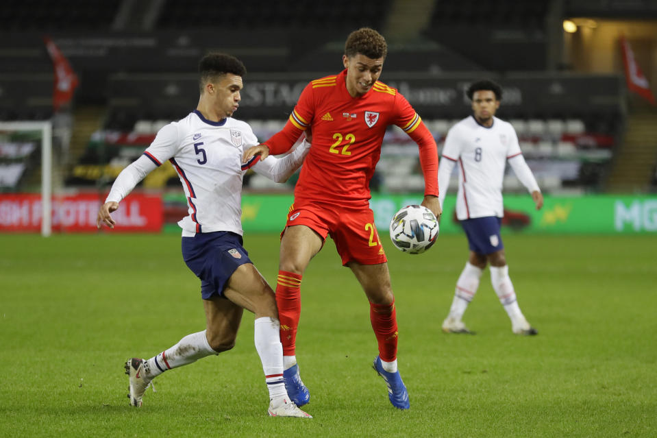 United States' Antonee Robinson vies for the ball with Wales' Brennan Johnson during the international friendly soccer match between Wales and USA at Liberty stadium in Swansea, Wales Thursday, Nov. 12, 2020. (AP Photo/Kirsty Wigglesworth)