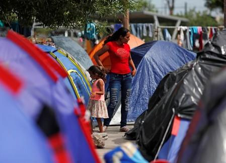 Central American migrants are seen outside their tents in an encampment in Matamoros