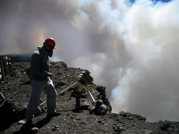 A geologist from the Hawaii Volcano Observatory checks on a time-lapse camera positioned at the rim of Halema'uma'u crater, at Kilauea's summit.