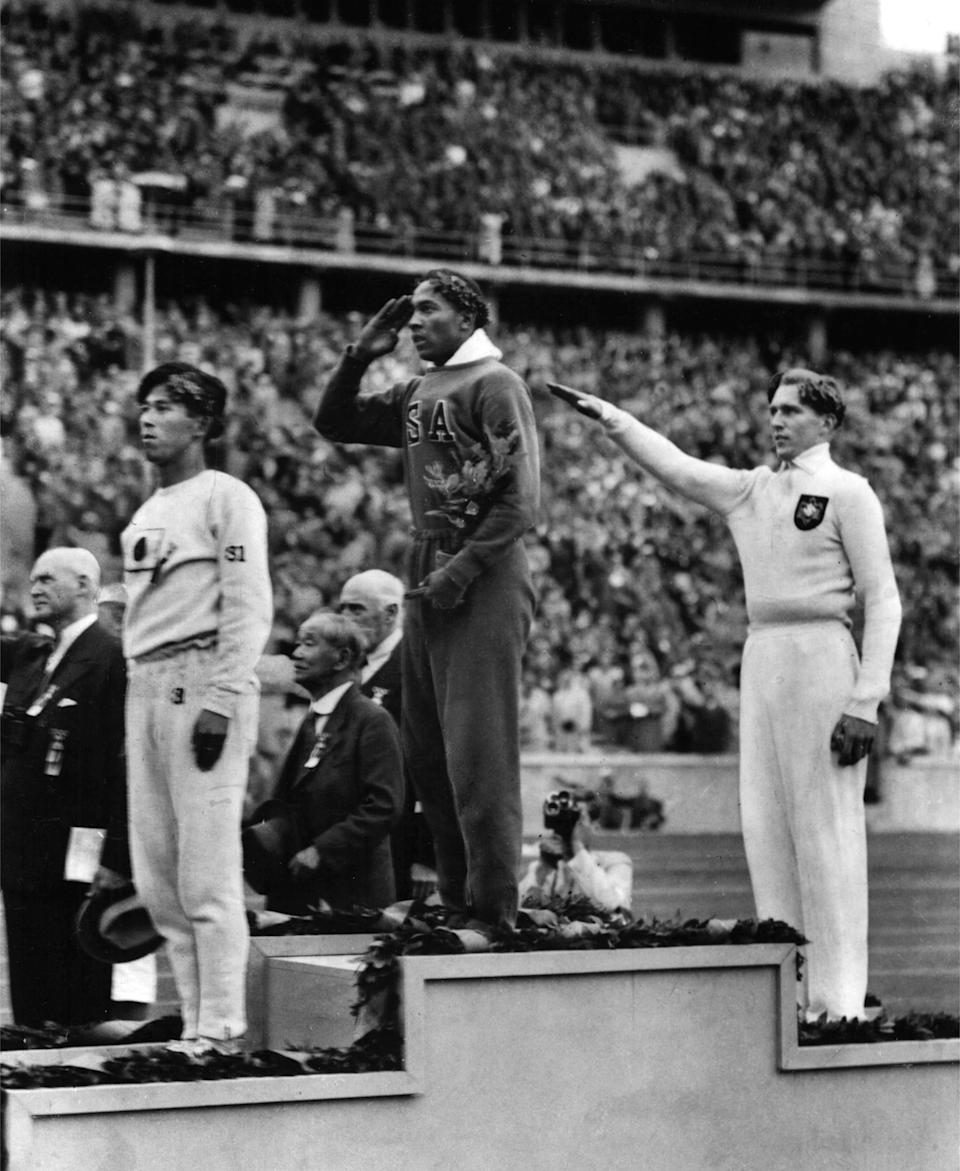 America's Jesse Owens, center, salutes during the presentation of his gold medal for the long jump on August 11, 1936, after defeating Nazi Germany's Lutz Long, right, during the 1936 Summer Olympics in Berlin. Naoto Tajima of Japan, left,  placed third. Owens triumphed in the track and field competition by winning four gold medals in the 100-meter and 200-meter dashes, long jump and 400-meter relay. He was the first athlete to win four gold medals at a single Olympic Games. (AP Photo)