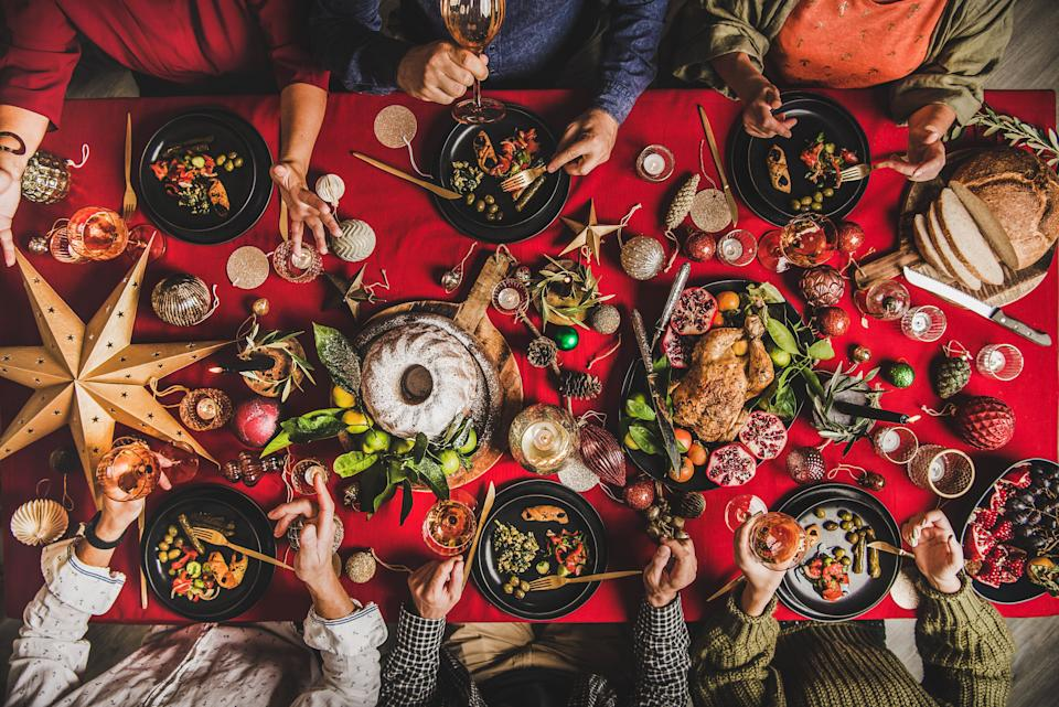 Friends celebrating Christmas. Flat-lay of people eating and talking over festive table with red cloth with champagne, roasted chicken, bundt cake, fruits, decorations, top view. Winter holiday party (Photo: Foxys_forest_manufacture via Getty Images)