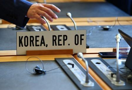 Members of the South Korea delegation arrive for the General Council meeting at the World Trade Organization (WTO) in Geneva