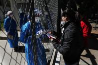 The relative of a COVID-19 patient hospitalized at Ineram Hospital's ICU, is given a list of prescription medication to buy from a doctor through the hospital fence in Asuncion, Paraguay, Monday, May 24, 2021. (AP Photo/Jorge Saenz)