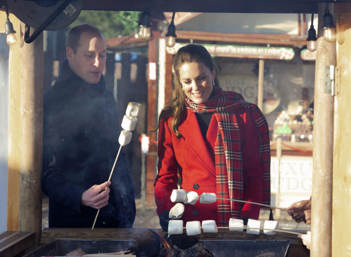Britain's Prince William and Kate, Duchess of Cambridge toast marshmallows during a visit to meet students at the 'Christmas at the Castle' event held at Cardiff Castle, Wales, Tuesday Dec. 8, 2020, to hear how they have been supported with their mental health during lockdown, on the final day of a three-day tour across the country. (Jonathan Buckmaster/Pool via AP)