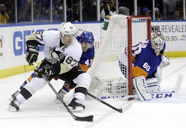 New York Islanders' Andrew MacDonald (47) defends Pittsburgh Penguins' Sidney Crosby (87) as he looks to pass away from goalie Kevin Poulin (60) during the first period of an NHL hockey game, Thursday, Jan. 23, 2014 in Uniondale, N.Y. (AP Photo/Frank Franklin II)