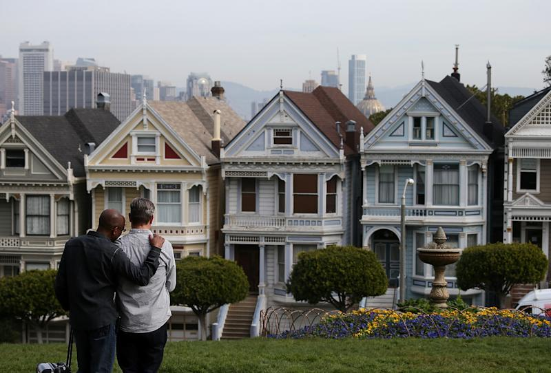 People stop to look at San Francisco's famed Painted Ladies victorian houses on February 18, 2014 in San Francisco, California