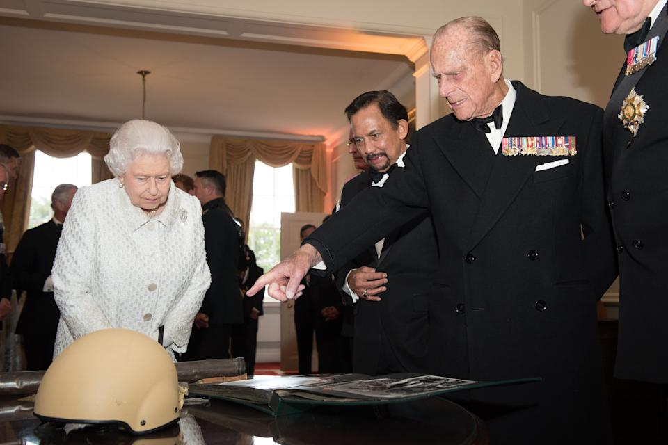 The Queen and Philip, alongside the Sultan of Brunei Hassanal Bolkiah, look at the damaged helmet worn by Corporal Tuljung Gurung of the First Royal Gurkha Regiment during the Gurkha 200 pageant in the grounds of the Royal Hospital Chelsea in London on June 9, 2015. (LEON NEAL/AFP via Getty Images)