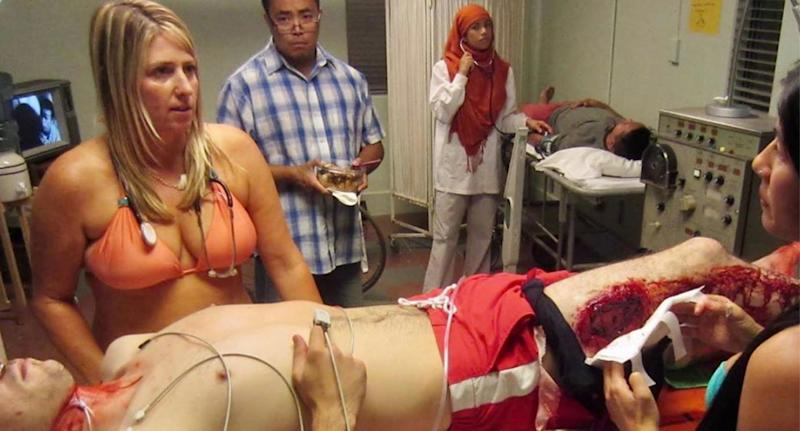 Pictured is Dr Candice Myhre standing over a bleeding man in a hospital room while wearing a bikini and stethoscope.