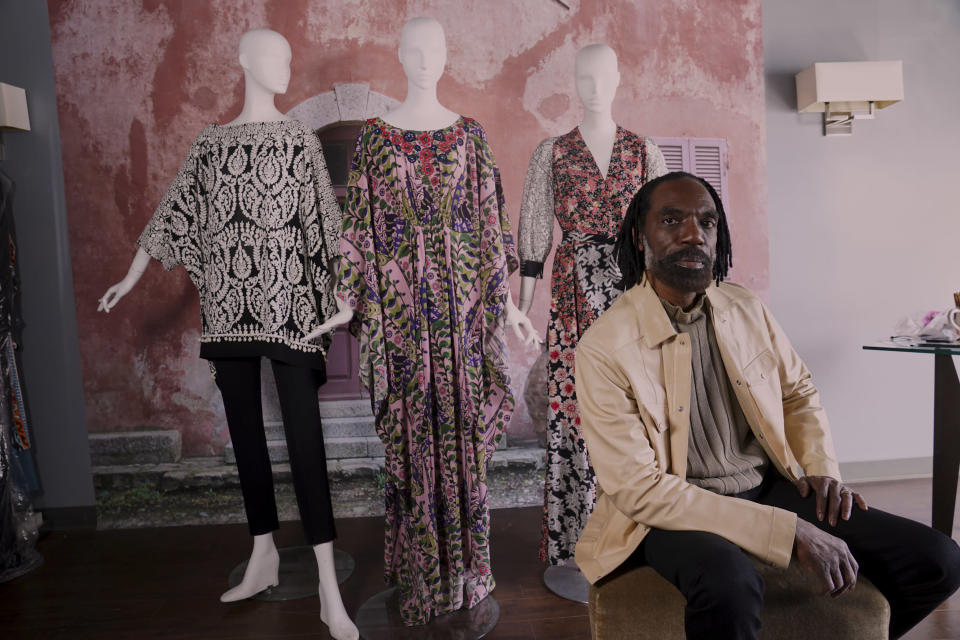 """Fashion designer Kevan Hall pauses for a picture at his """"Luxe Leisure Collection"""" haute couture atelier in West Los Angeles Thursday, March 18, 2021. A year ago, Hall quickly moved away from his trademark gowns and cocktail dresses to caftans, tunics and pull-on pants. Now Hall is adding back some dressier looks, but he's eliminating the full skirts and scaling back the beading in favor of simple gowns and dresses in knit and tulle fabrics. (AP Photo/Damian Dovarganes)"""