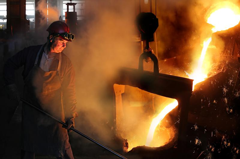 A man working in a steel mill with molten steel being poured