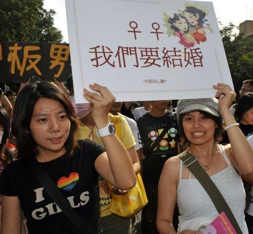"""File photo shows lesbians carrying a placard reading """" We want to marry"""" during an annual gay parade in Taipei. Two women plan to tie the knot next month in Taiwan's first same-sex Buddhist wedding, as gay and lesbian groups push to make the island the first society in Asia to legalise gay marriage"""