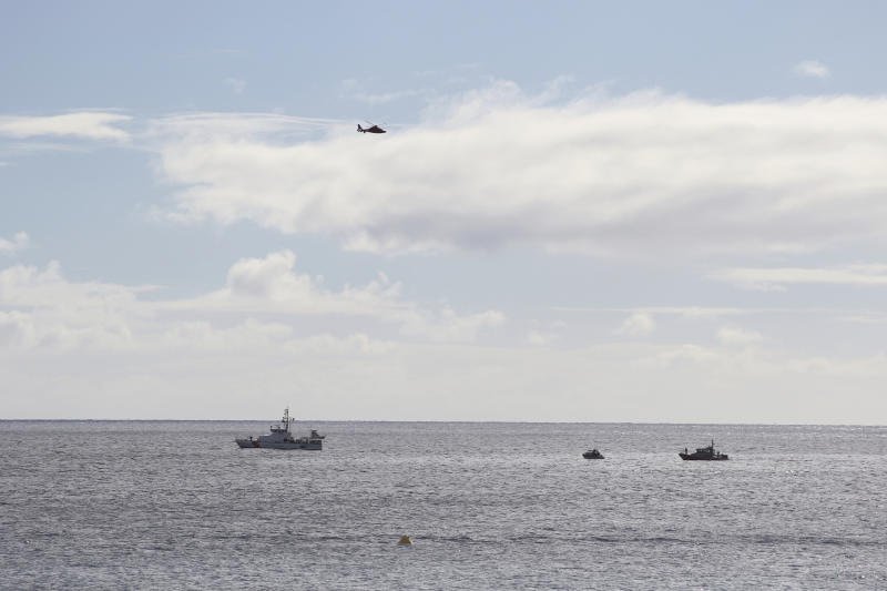 A U.S. Coast Guard helicopter flies over rescue boats at the scene of plane crash off Honolulu, Wednesday, Dec. 12, 2018. Federal Aviation Administration spokesman Ian Gregor said a Hawker Hunter jet went down in the ocean around 2:25 p.m. after taking off from Honolulu's airport. U.S. Coast Guard spokeswoman Petty Officer Sara Muir said the pilot is in stable condition after being rescued about 3 miles (4.8 kilometers) south of Oahu near Honolulu's Sand Island. (AP Photo/Caleb Jones)
